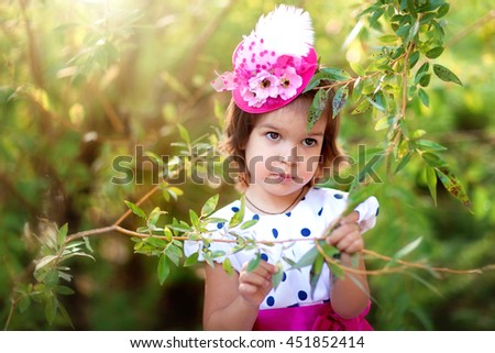Adorable little fashion girl in a pink hat and polka-dot dress. Beautiful kid on green colorful background. Sun light.