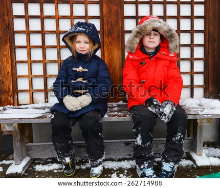 Adorable little girl and cute boy outdoors on beautiful winter day - stock photo