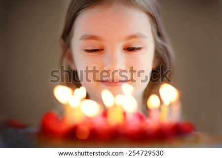 Adorable little girl and her delicious raspberry birthday cake - stock photo