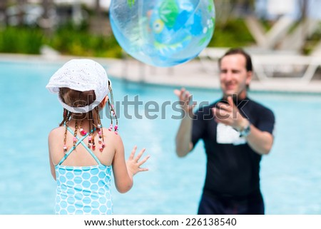 Adorable little girl and her father at swimming pool playing with ball - stock photo