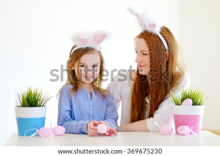 Adorable little girl and her mother wearing bunny ears on Easter day - stock photo