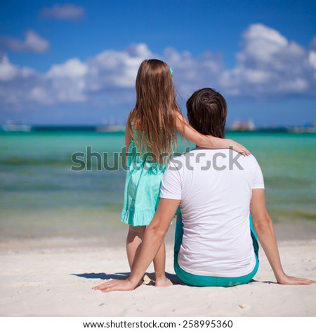 Adorable little girl and young dad at tropical beach - stock photo