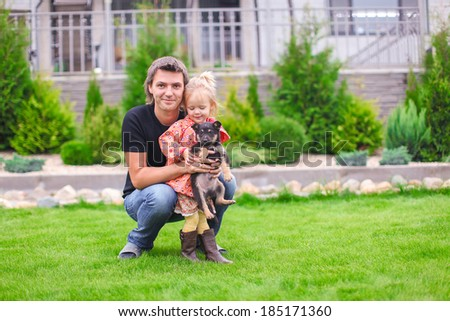 Adorable little girl and young father with puppy outdoor - stock photo