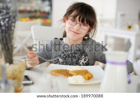 Adorable little girl at restaurant having breakfast - stock photo