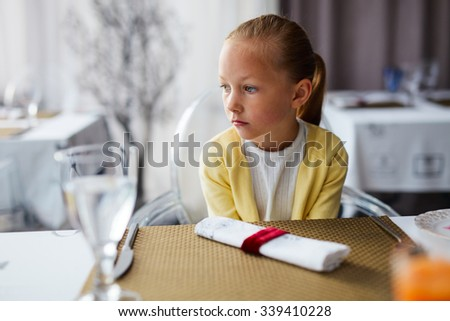 Adorable little girl at restaurant waiting for an order