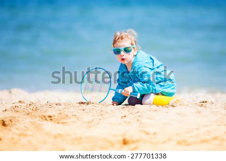 Adorable little girl at the beach playing with sand
