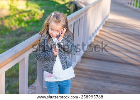 Adorable little girl at warm autumn day outdoors - stock photo