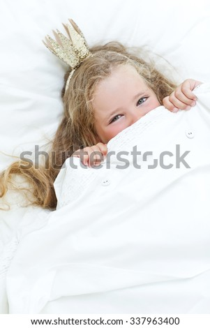 Adorable little girl awaked up in her bed - stock photo