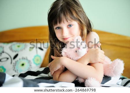 Adorable little girl awaked up in her bed on sunny morning - stock photo