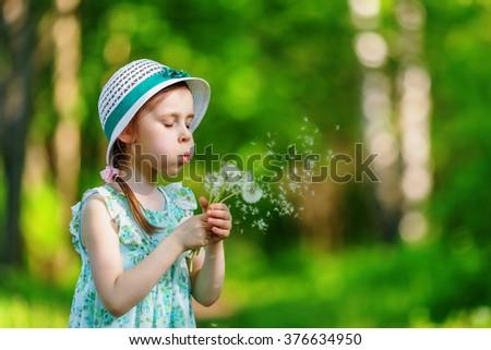 Adorable little girl blowing dandelion in summer park - stock photo