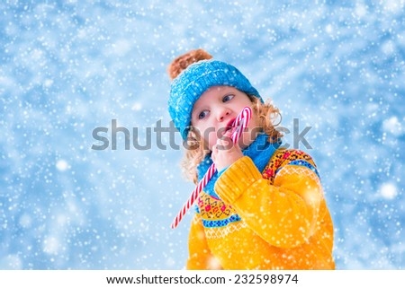 Adorable little girl, cute toddler in a blue knitted hat and yellow sweater, eating Christmas red sugar candy and playing with snow catching snowflakes having fun outdoors in a beautiful winter park - stock photo