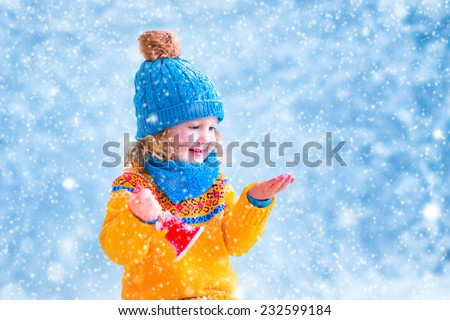 Adorable little girl, cute toddler in a blue knitted hat and yellow sweater, playing with snow, catching snowflakes and ringing her Christmas toy bell, having fun outdoors in a beautiful winter park - stock photo