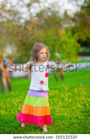 Adorable little girl dancing in the park - stock photo