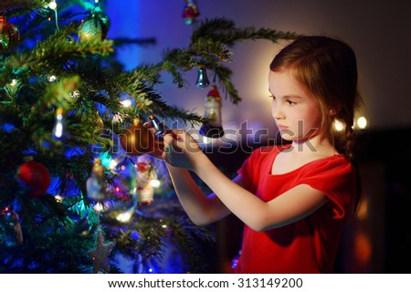 Adorable little girl decorating a Christmas tree with colorful glass baubles at home - stock photo