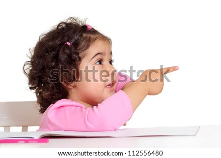 Adorable little girl draws with colored pencils sitting at the table - stock photo