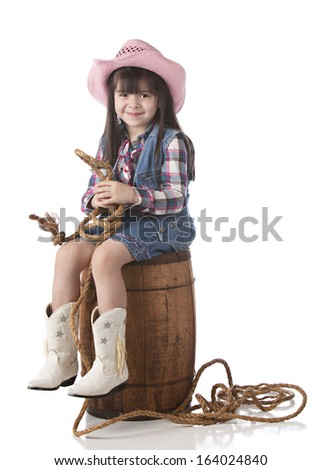 Adorable little girl dressed as a cowgirl.  Isolated on white.
