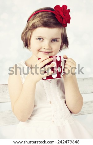 Adorable little girl drinking cocoa from red cup - stock photo