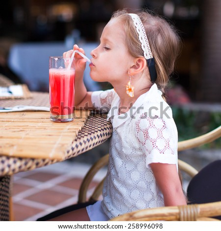 Adorable little girl drinking fruit cocktail outdoor - stock photo
