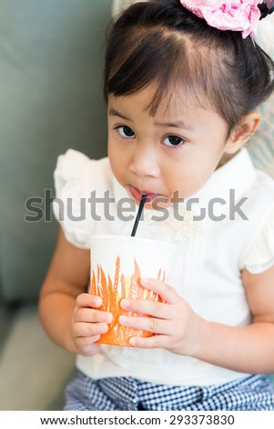 Adorable little girl drinking juice with paper cup - stock photo