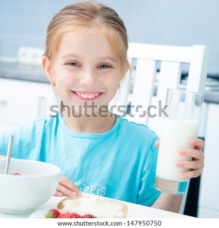 adorable little girl drinking milk in the kitchen - stock photo