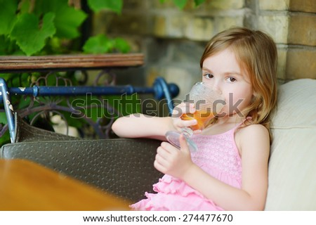Adorable little girl drinking orange juice in an outdoor cafe on warm and sunny summer day - stock photo