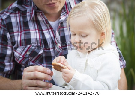 Adorable Little Girl Eating a Cookie with Daddy Outside. - stock photo