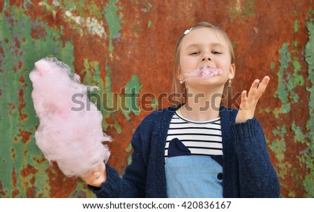 Adorable little girl eating candy-floss