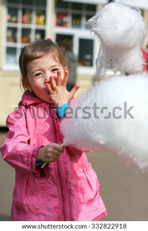 Adorable little girl eating candy-floss outdoors. Selective focus  - stock photo