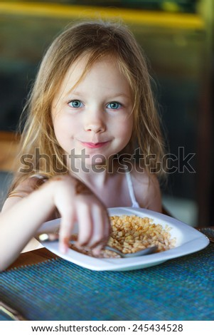 Adorable little girl eating cereal with a milk for a breakfast in restaurant - stock photo