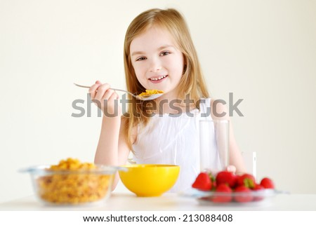 Adorable little girl eating cereal with strawberries and drinking milk in white kitchen - stock photo