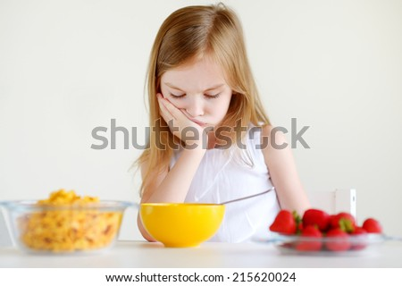 Adorable little girl eating cereal with strawberries in white kitchen
