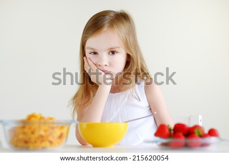 Adorable little girl eating cereal with strawberries in white kitchen - stock photo