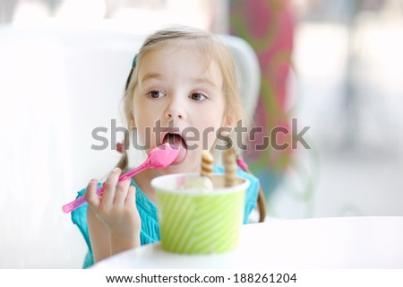 Adorable little girl eating ice cream at summer - stock photo