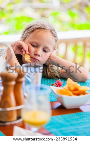Adorable little girl eating potato chips at lunch restaurant - stock photo