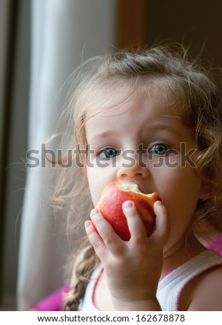 Adorable little girl eating red apple - stock photo