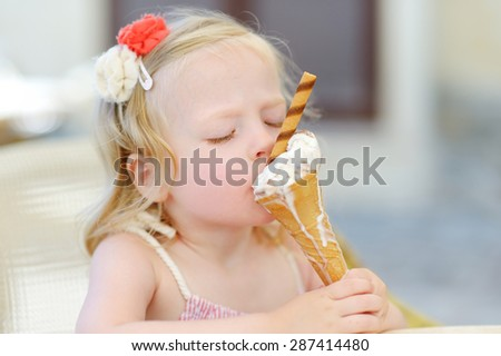 Adorable little girl eating tasty fresh ice cream outdoors on warm sunny summer day - stock photo