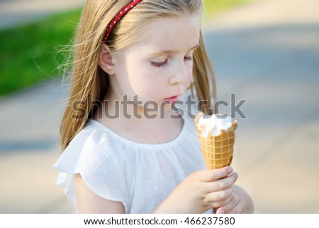 Adorable little girl eating tasty ice cream at park on warm sunny summer day