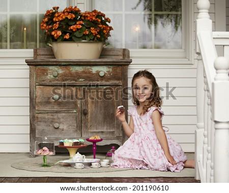 Adorable little girl enjoying a tea party on the porch. - stock photo