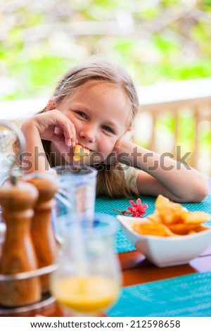 Adorable little girl enjoying eating potato chips at restaurant - stock photo