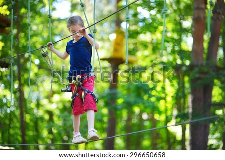 Adorable little girl enjoying her time in climbing adventure park on warm and sunny summer day - stock photo
