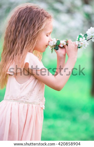 Adorable little girl enjoying smell in a flowering cherry spring garden