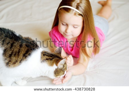 Adorable little girl feeding her cat