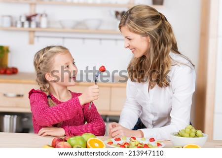 Adorable little girl feeding her mother a delicious ripe red strawberry as they have fun together in the kitchen preparing a fresh fruit salad - stock photo