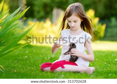 Adorable little girl feeding small kitten with kitten milk from the bottle at summer day