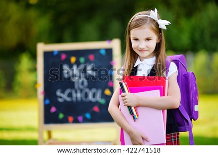 Adorable little girl feeling very excited about going back to school - stock photo