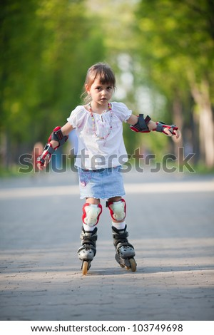 Adorable little girl gains confidence on rollerblades - stock photo