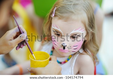 Adorable little girl getting her face painted - stock photo