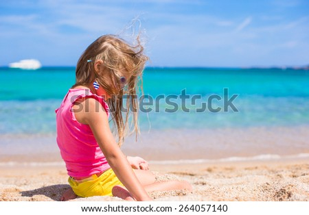 Adorable little girl have fun at tropical beach during vacation - stock photo