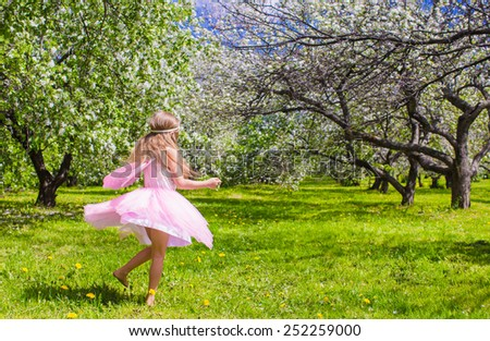 Adorable little girl have fun in blossoming apple tree garden - stock photo