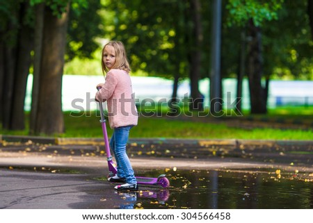 Adorable little girl have fun on the scooter outdoor - stock photo
